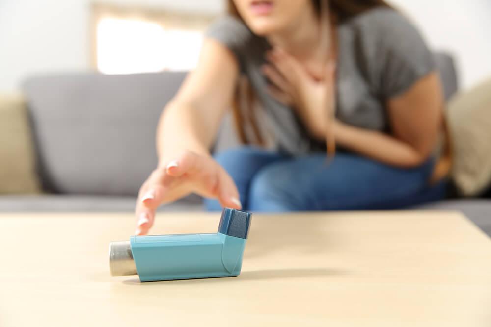Mujer cogiendo el inhalador por problemas de asma