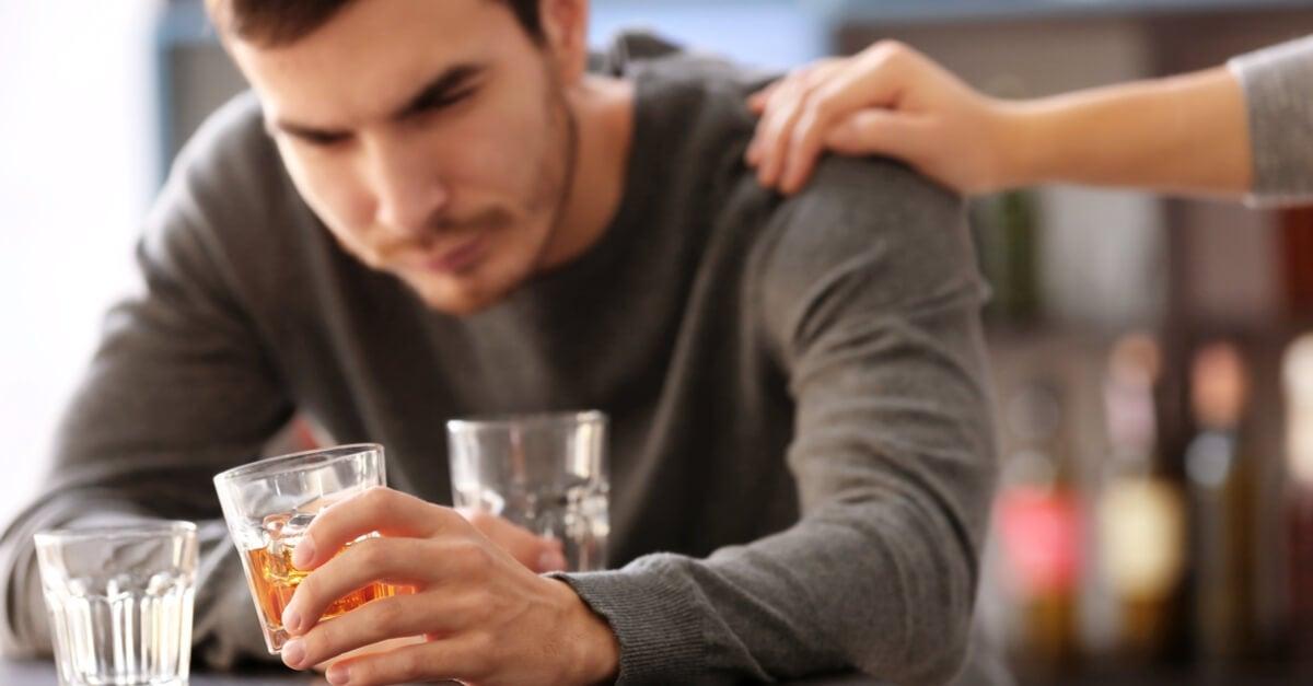 Hombre con vasos de alcohol en las manos