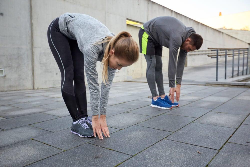 Mujer y hombre estirando sus piernas con las manos en el suelo