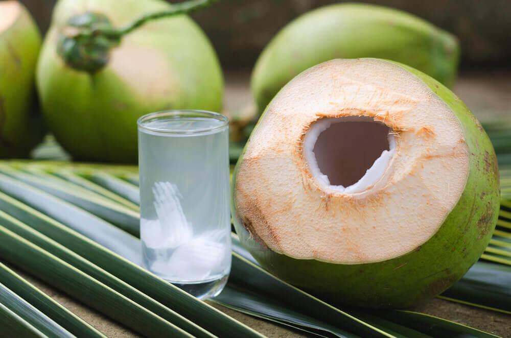 Vaso de agua de coco verde con limón.