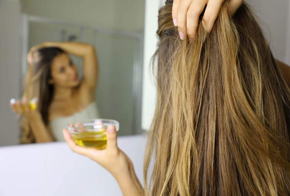 Chica aplicándose aceite en el cabello.