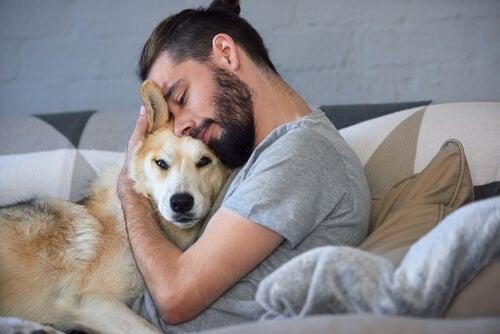 Chico abrazando a su perro en la cama.