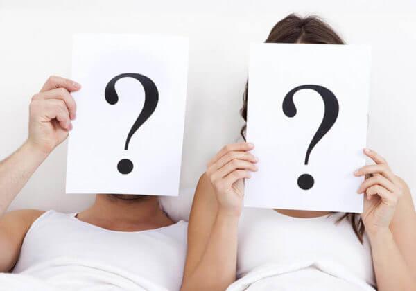 Pareja en la cama con signos de interrogación