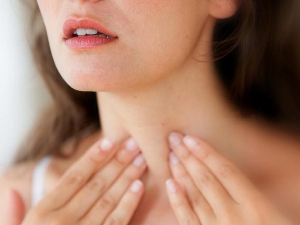 Mujer explorándose la tiroides.