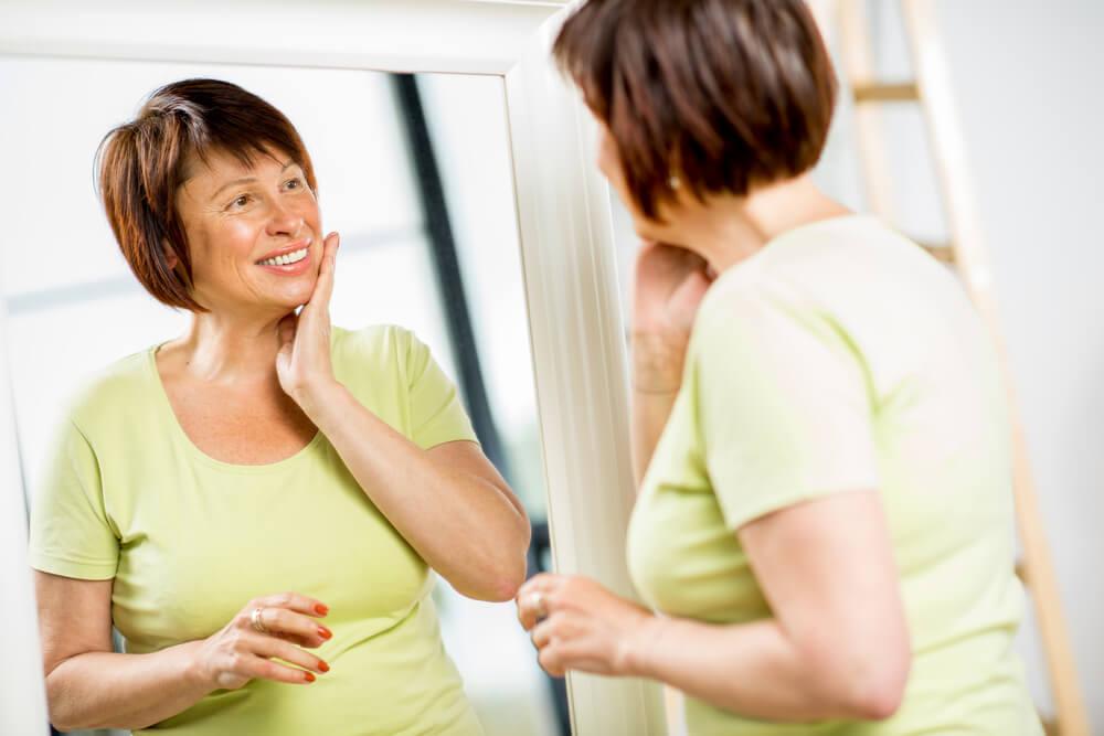 Mujer sonriéndose frente a un espejo