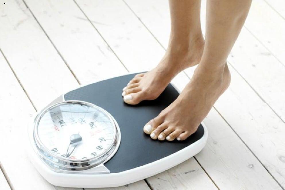 Mujer en la báscula comprobando si ha perdido peso después de seguir una dieta cetogénica