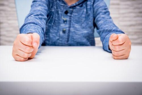 Puños de un niño en la mesa