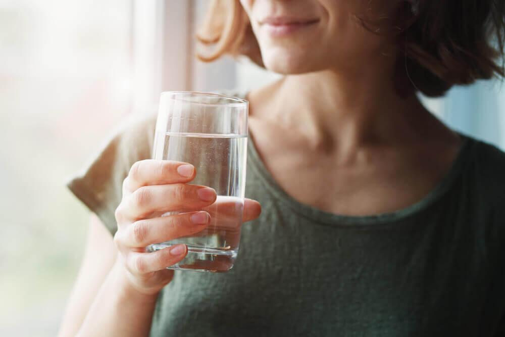 Mujer sosteniendo un vaso con agua que va a beber.