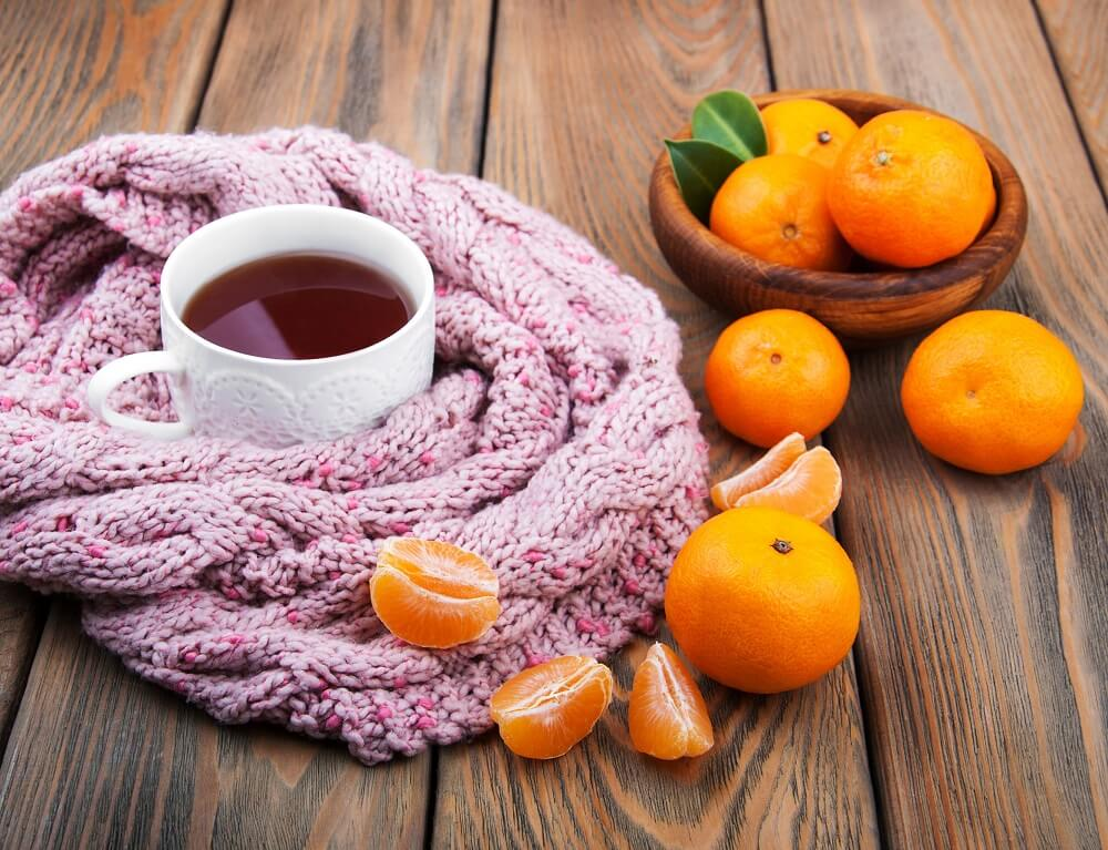 51270705 - cup of tea with scarf and tangerines on a old wooden table