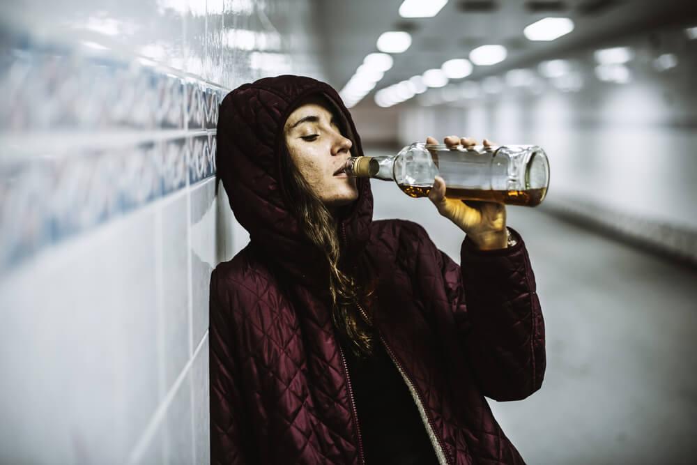 Mujer bebiendo alcohol de una botella