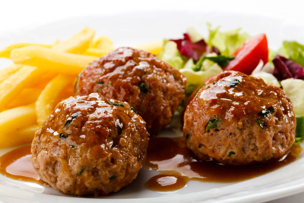 Plato con albóndigas en salsa, patatas y ensalada.