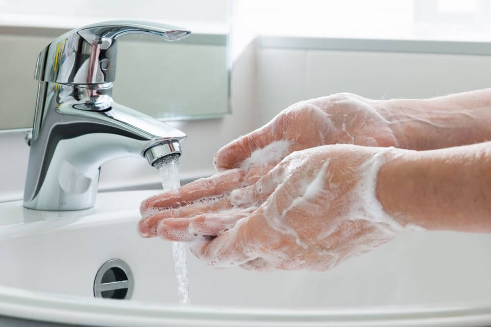 Manos enjabonadas debajo del chorro de agua de un grifo.