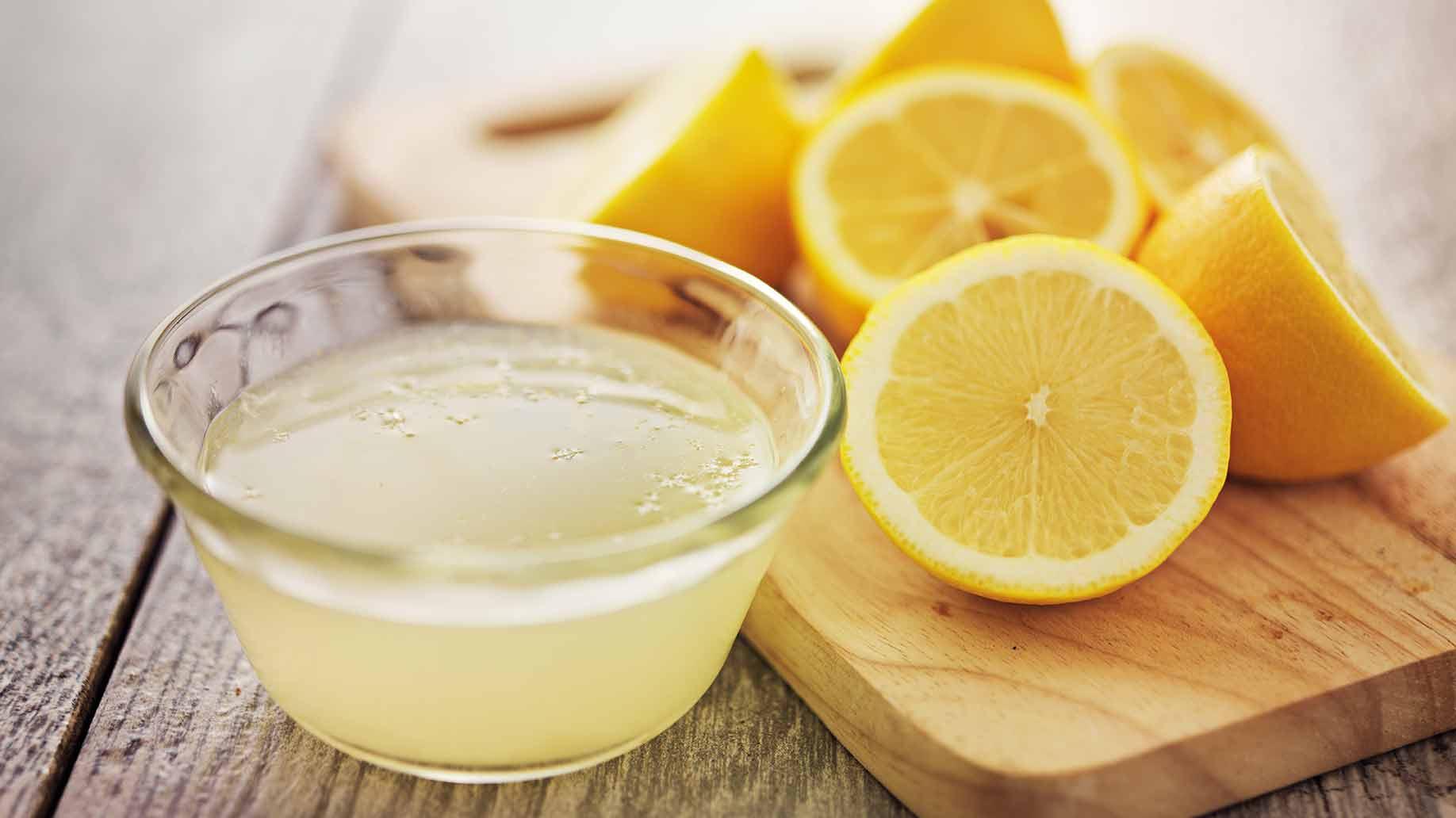 Zumo de limón y limones cortados