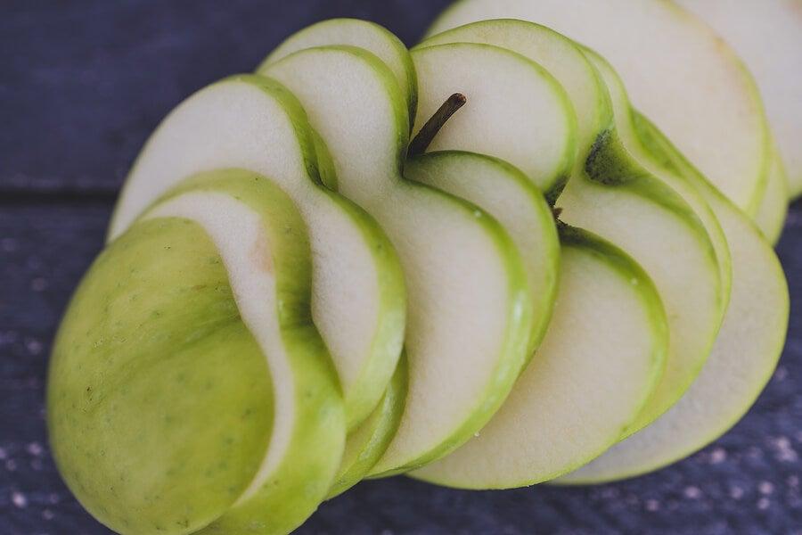 Manzana verde cortada en forma de corazones.