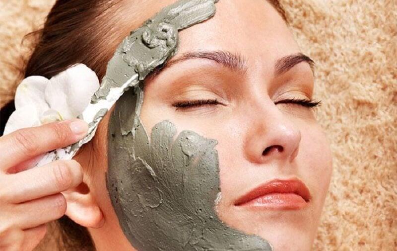 Mujer echándose arcilla en la cara.