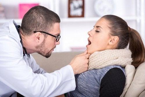 Médico mirando la garganta de una mujer