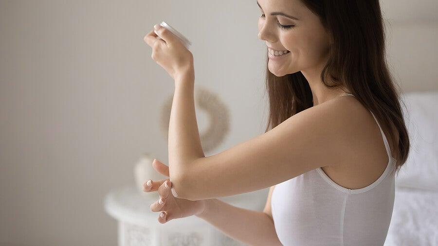 Mujer aplicándose crema en los cojos