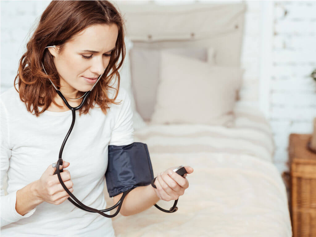 Mujer tomándose presión arterial