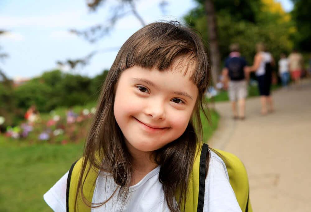 Niña con síndrome de Down con mochila para ir al colegio.