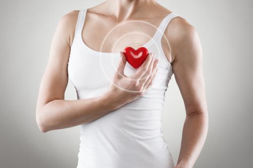 Mujer sosteniendo un corazón de goma, indicando salud.