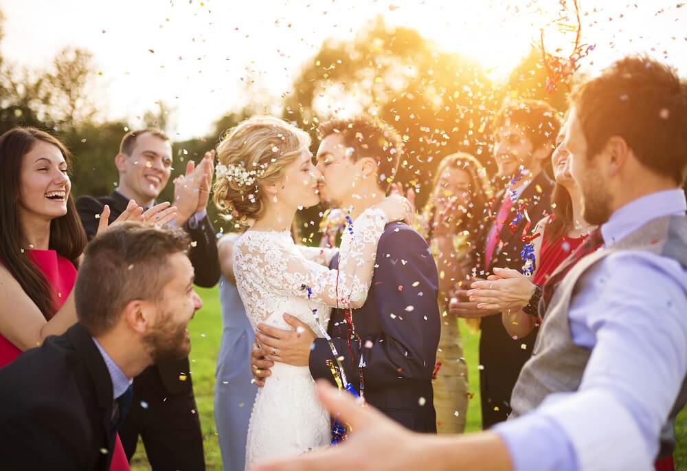 Novio y novia en a boda besándose rodeados de los invitados