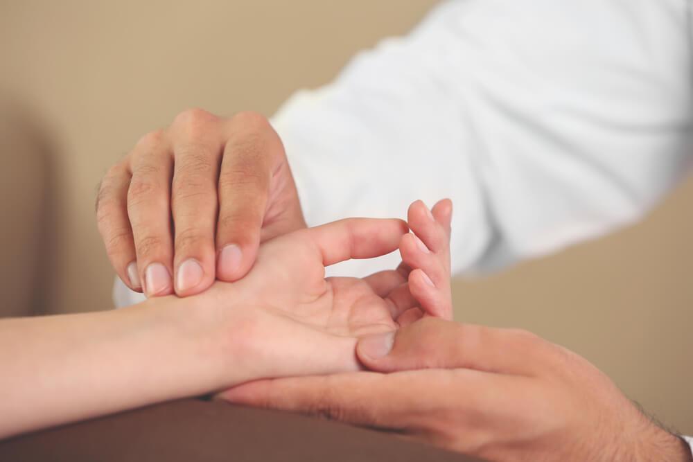 Médico fazendo tratamento para a tendinite devido à lactação