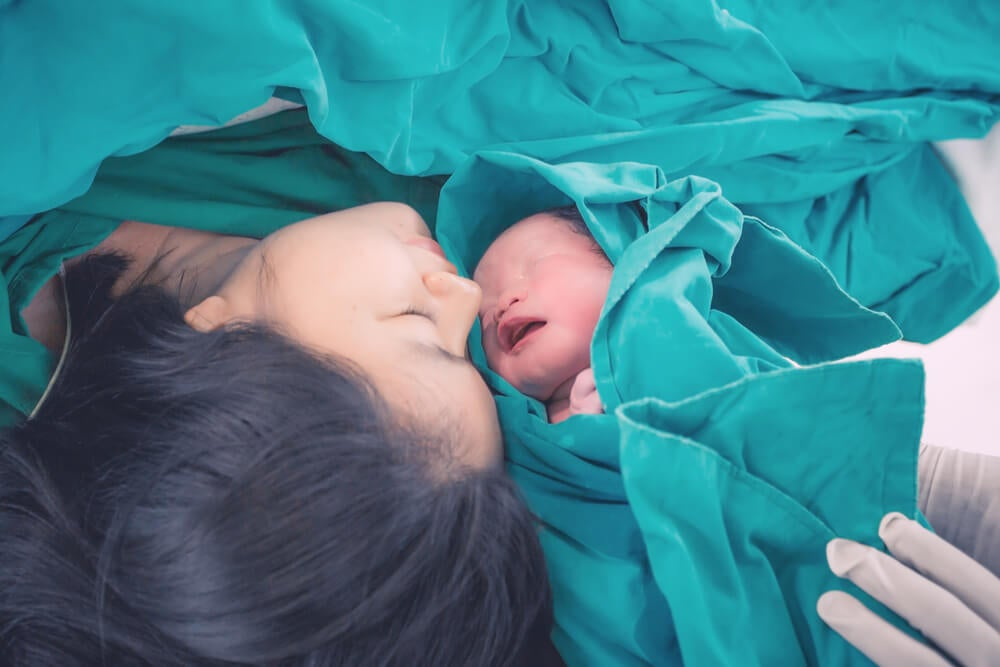 Mulher recebendo seu filho após uma cesariana