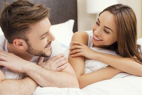 Pareja mirándose y sonriendo encima de la cama
