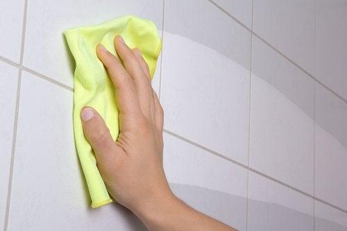 Mano limpiando la pared con un trapo