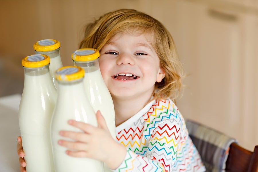 Niño con botes de leche.