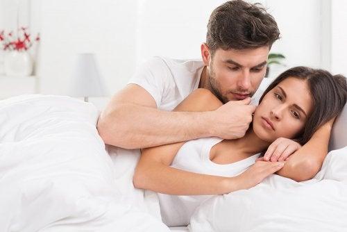Pareja en la cama donde el hombre está consolando a la mujer