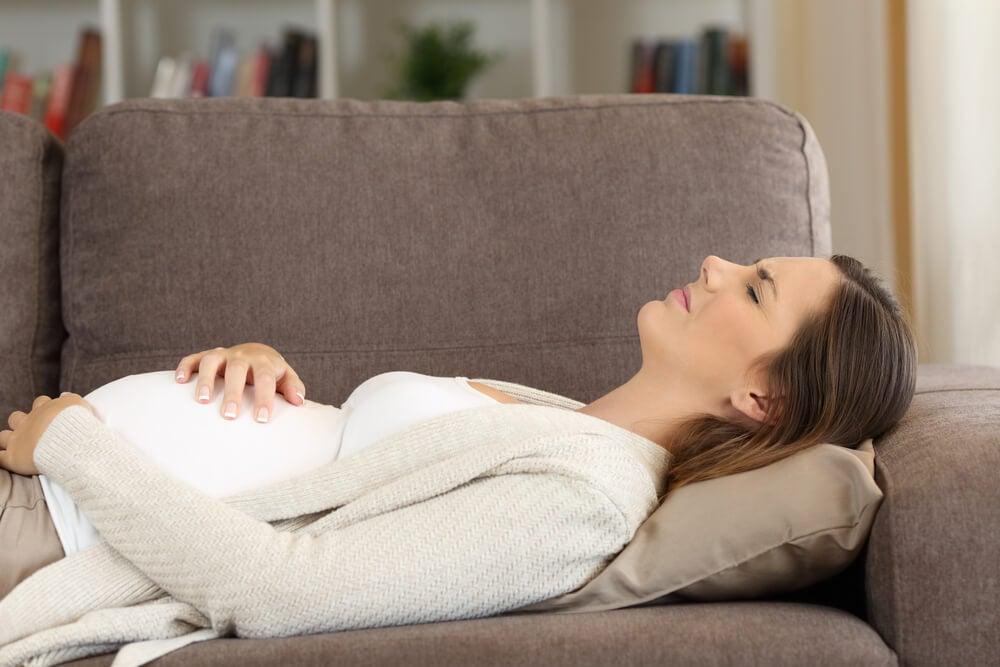 Mujer embaraza tumbada en el sofá con molestias. Típicos cólicos en el embarazo.
