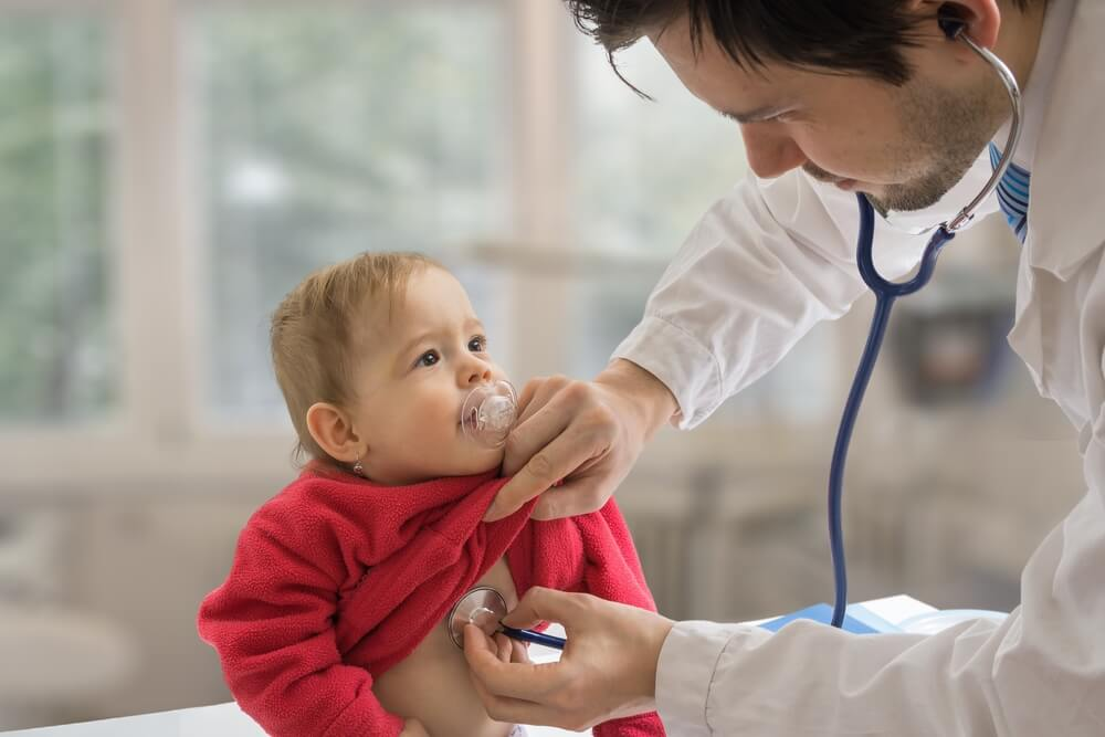Médico observando a un niño con neumonía.