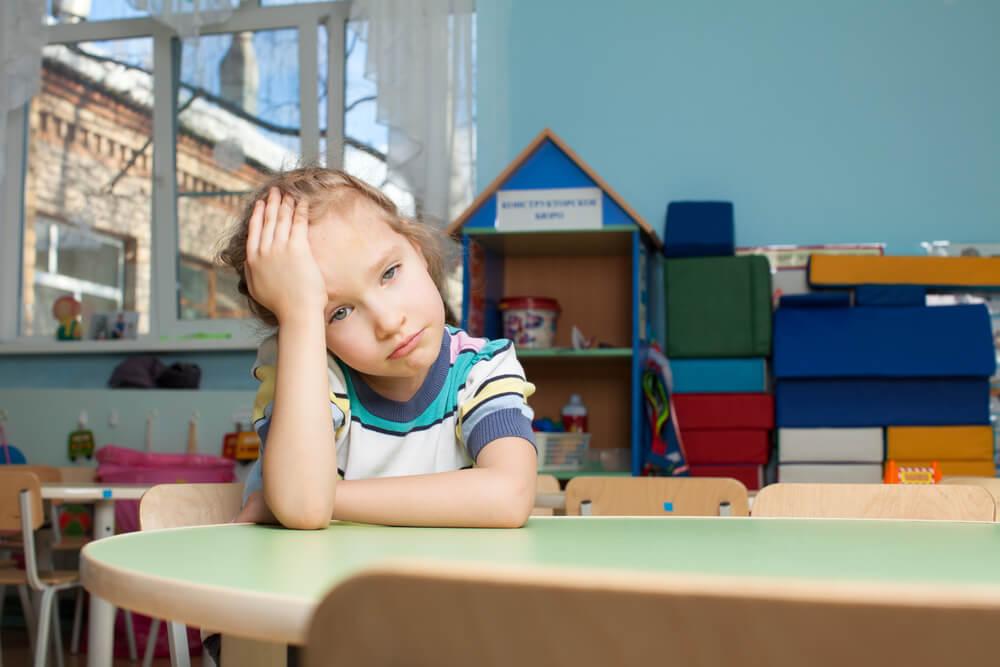Niña sentada en una mesa del colegio se sujeta la cabeza con expresión triste o frustrada.