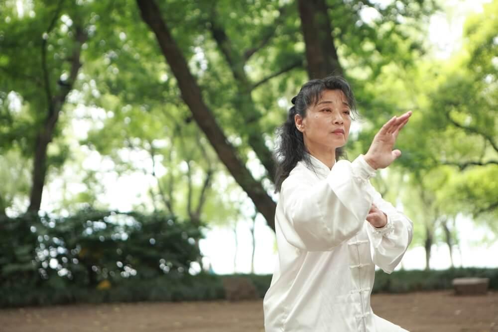 Mujer practicando taichí en un parque
