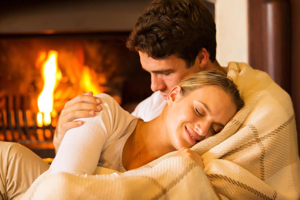 Pareja abrazada junto al fuego