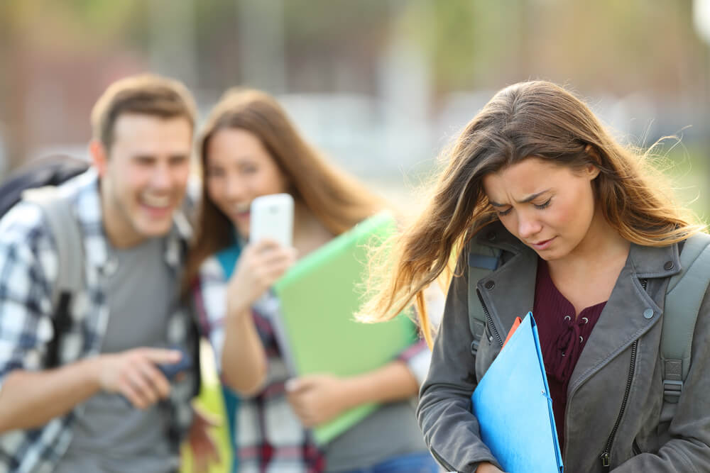 Un síntoma de bullying emocional es cuando una persona o grupo de personas habla mal de ti a tus espaldas pero es agradable contigo