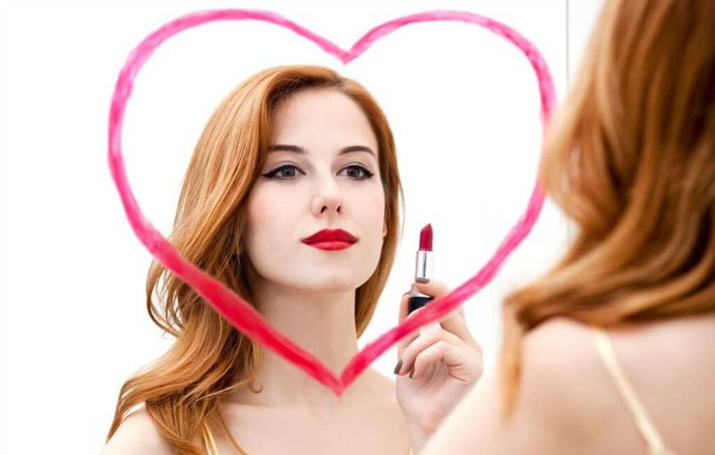 Chica mirándose en un espejo con un pintalabios