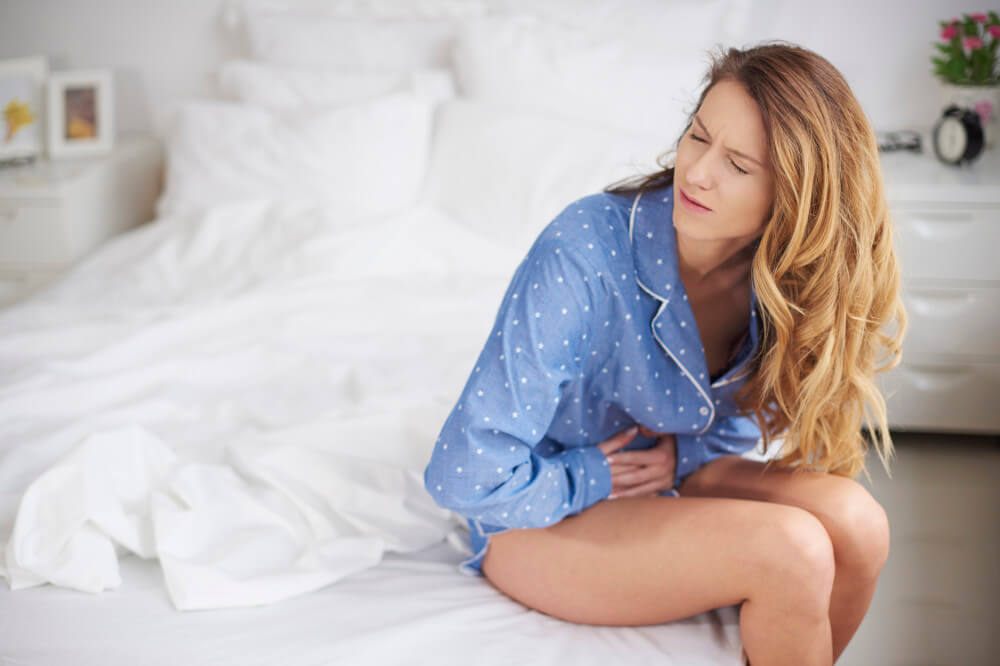 A woman with pain in the abdomen sitting on the bed.