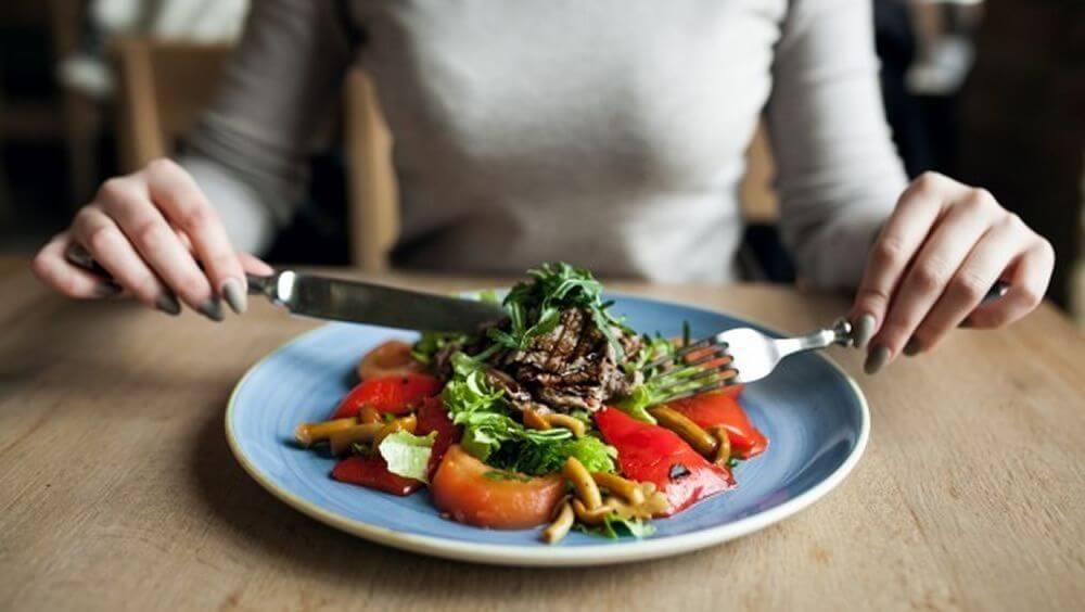 Mujer en la mesa siguiendo una buena alimentación