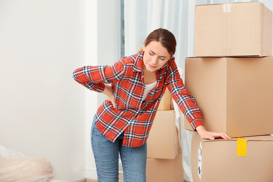 Young woman suffering from pain after moving heavy box