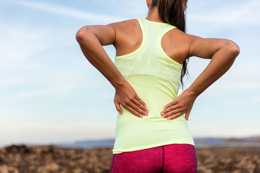 Trail running runner with painful lower back pain injury or stra