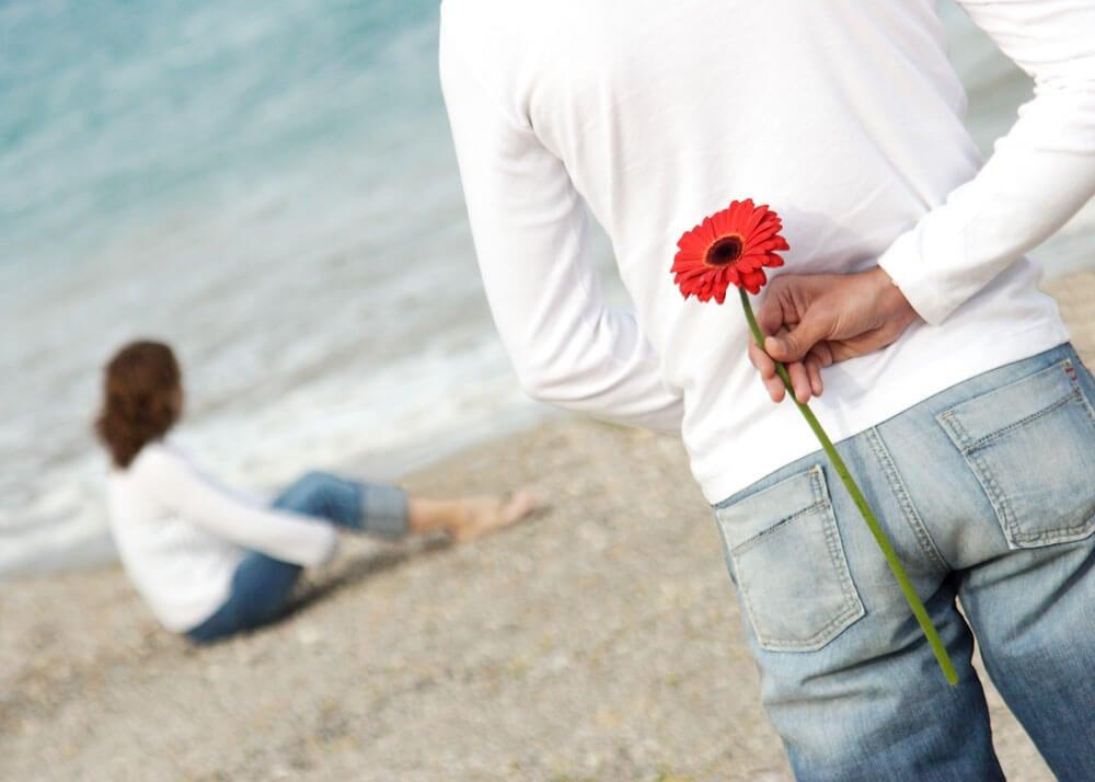 Hombre con una flor a la espalda acercándose a una chica.