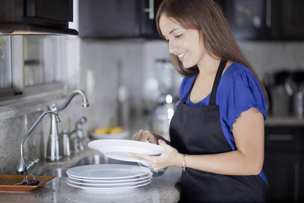 Lavar los platos a mano.