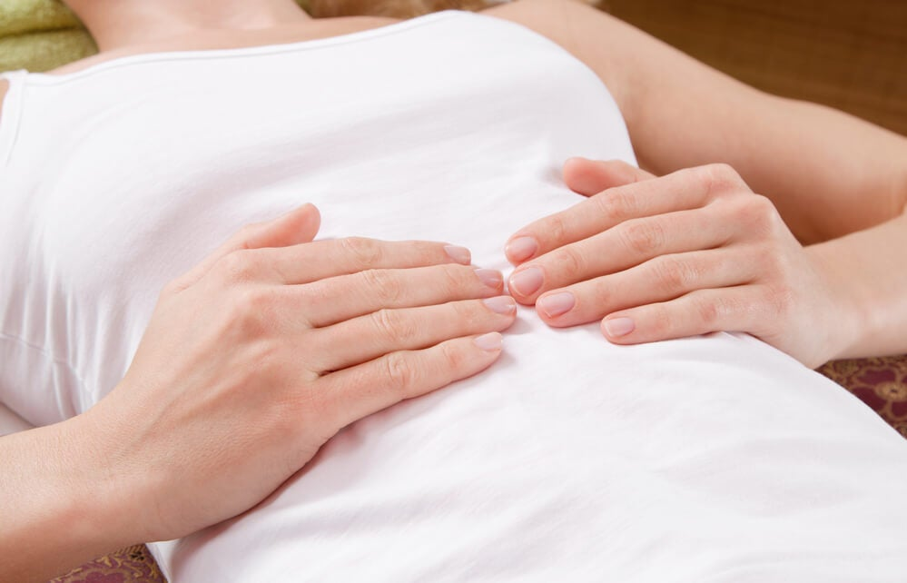 Hands of lying woman on her belly during massage