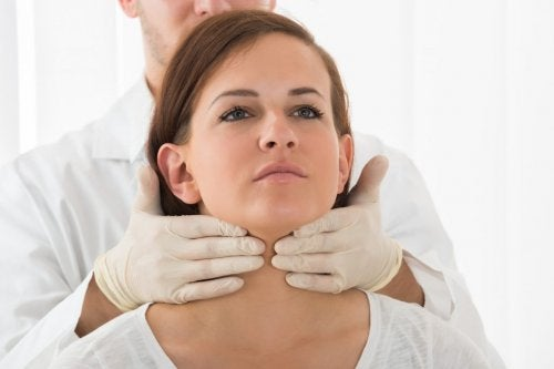 Médico auscultando la tiroides de una mujer