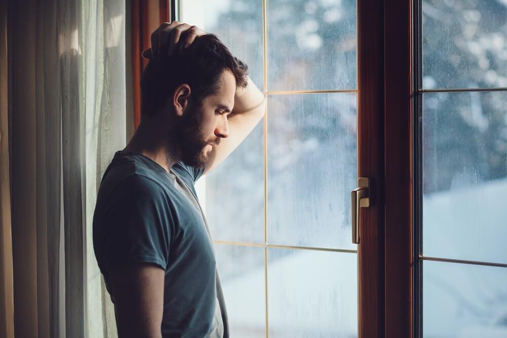 Hombre en la ventana triste autoengañamos