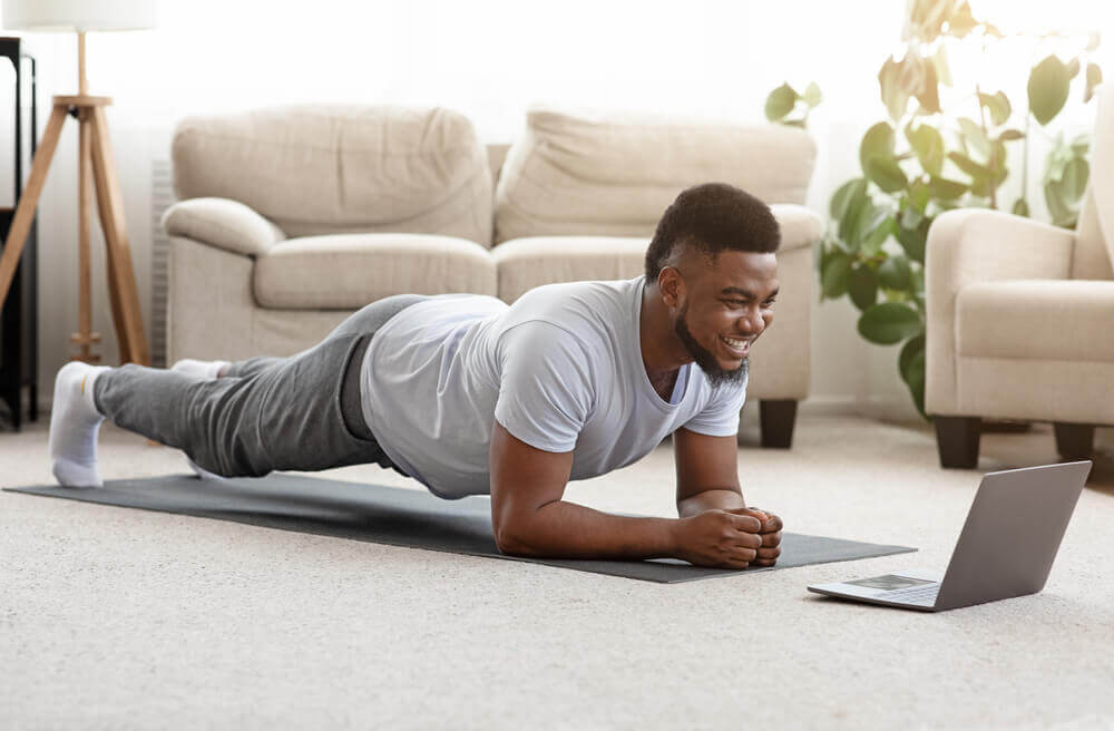 Hombre sobre una esterilla haciendo ejercicios en casa.