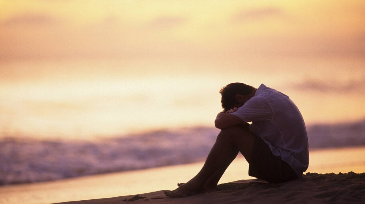 Hombre triste sentado en la orilla del mar