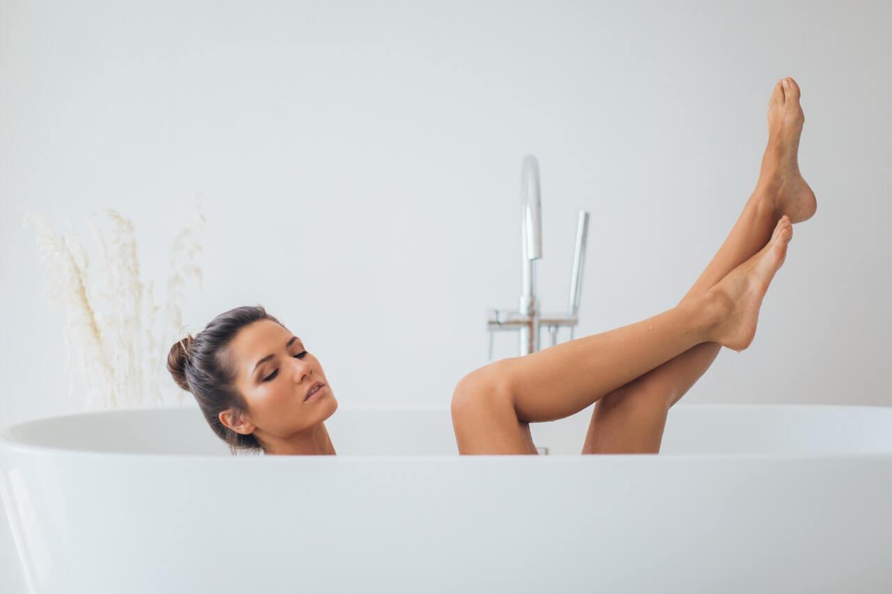 Mujer relajándose en una bañera, concediéndose tiempo a sí misma.
